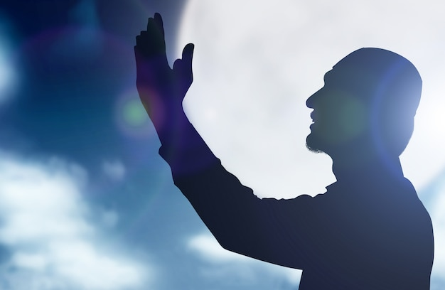 手を上げて立って、夜のシーンの背景で祈るイスラム教徒の男性のシルエット