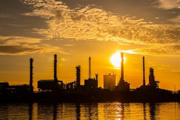 キラキラの照明と朝の日の出と石油と天然ガスの製油所産業プラントのシルエット