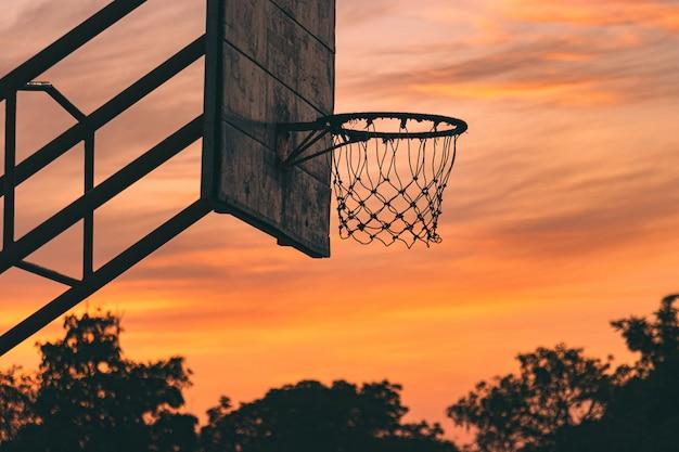 일출 아침에 극적인 하늘과 오래 된 야외 농구 코트의 실루엣