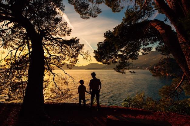 Силуэт родителей и двоих детей в море на закате в монтене