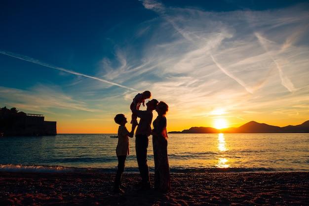 日没時の海で両親と2人の子供のシルエット。アドリア海のモンテネグロ。