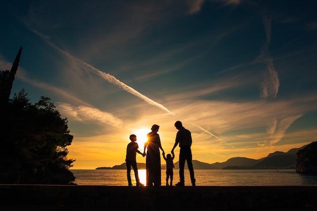 Силуэт родителей и двоих детей в море на закате
