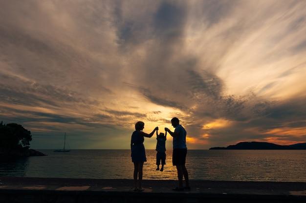 ビーチで海の家族で子供を持つ両親のシルエット私