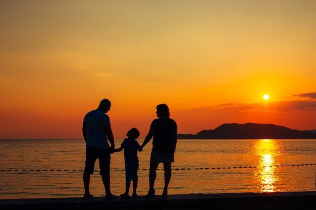 ビーチで海の家族で子供を持つ両親のシルエット