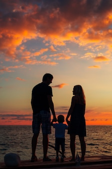 海で子供を持つ親のシルエット
