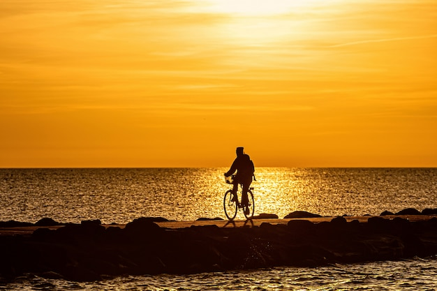 Силуэт людей на велосипеде на пирсе во время золотого часа заката