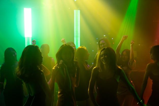 디스코 나이트 클럽에서 무대에서 dj의 음악에 맞춰 춤을 추는 사람들의 실루엣
