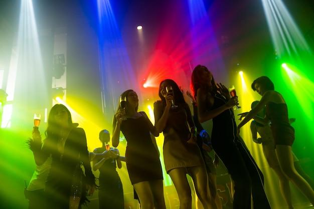Силуэт людей танцует в ночном клубе диско под музыку от ди-джея на сцене