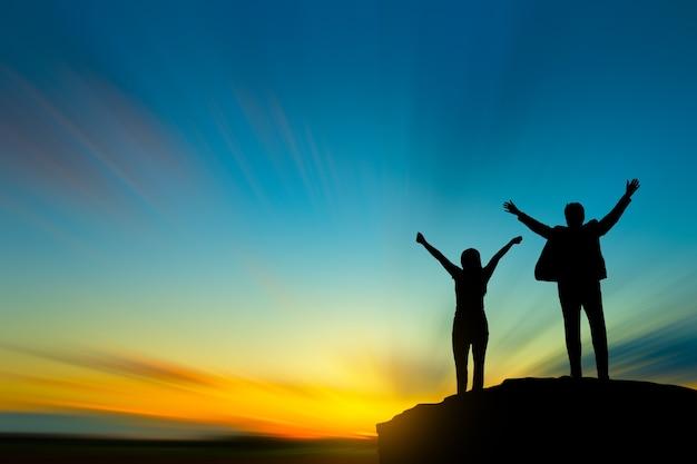 하늘과 태양 빛을 통해 산 위에 사람들의 실루엣
