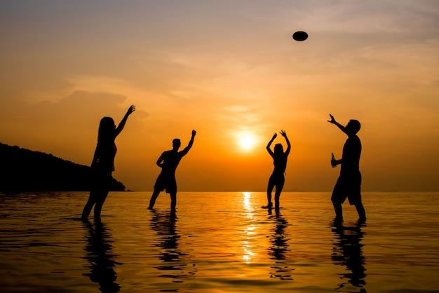 황혼의 일몰 해변에서 놀고 사람들의 실루엣