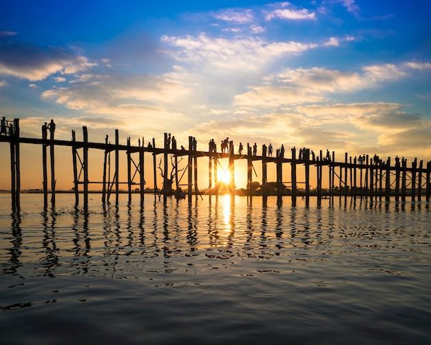 U bein橋、マンダレー、ミャンマーで日没時に歩く人のシルエット。