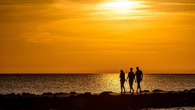 Силуэт людей, идущих на пирсе во время золотого часа заката