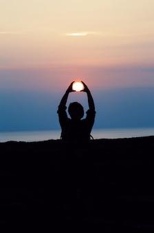 ゴールデンアワーの間に太陽をトレース彼の頭の上に両手で人のシルエット