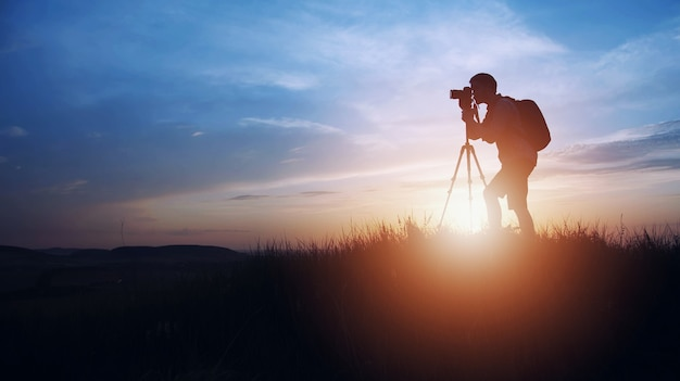 日没または日の出にデジタル一眼レフカメラと三脚を使用して写真を撮る写真家のシルエット