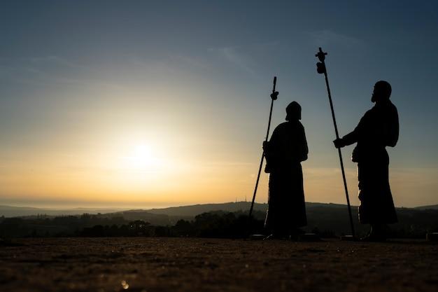 몬테 도 고조(monte do gozo)에 있는 스페인 산티아고 데 콤포스텔라(santiago de compostela)로 가는 길에 일몰 때 순례자의 실루엣.