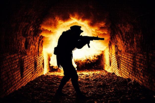 Силуэт постапокалиптического солдата или выжившего, стреляющего из автоматического огнестрельного оружия в темном подземелье, городских канализационных туннелях или подземном бункере с огнем взрыва и дымом на заднем плане