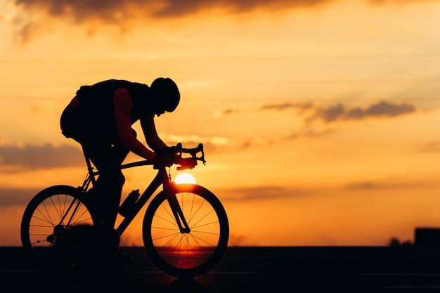 舗装道路でのスポーツ活動に自転車を使用して保護ヘルメットのプロのサイクリストのシルエット