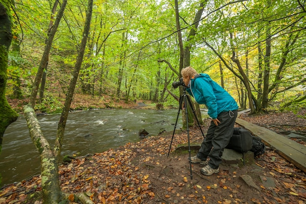 숲에서 강의 사진을 찍는 전문 사진 작가의 실루엣