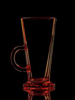 黒の背景にクリッピングパスで撮影するための赤いガラスのシルエット。