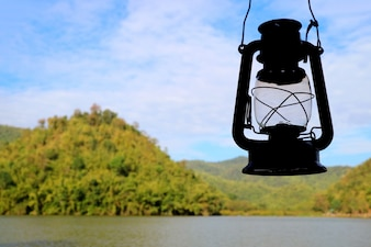 Silhouette of retro oil lantern against the morning sky of Hoob Khao Wong Reservoir, Thailand
