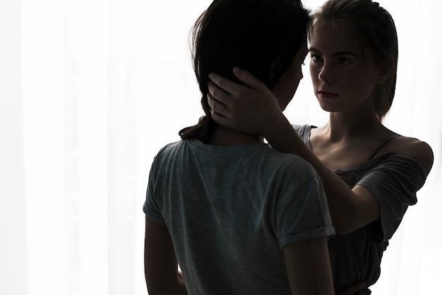 로맨틱 젊은 레즈비언 커플의 실루엣 서로 흰색 커튼에 대해 서보고
