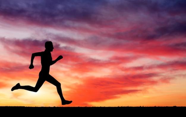 Силуэт бегущего человека против красочного неба. силуэт бегущего человека на закате огненном фоне