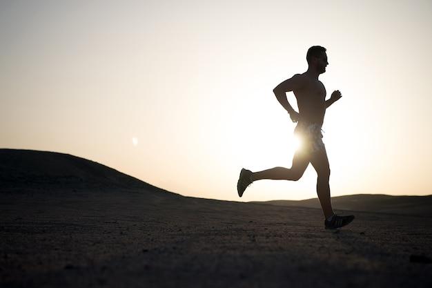 Силуэт бегущего человека на фоне огненного неба заката в горах, спорт и отдых, будущее и успех, люди и природа, скорость и здоровый образ жизни