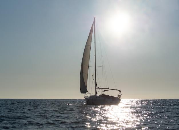 일몰 배경에서 빛나는 바다 물에 항해 요트의 실루엣