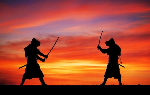 Силуэт самураев на дуэли. картина с двумя самураями и закатным небом