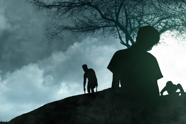 夜景を背景に立っている彼の体に血と傷を持つ恐ろしいゾンビのシルエット