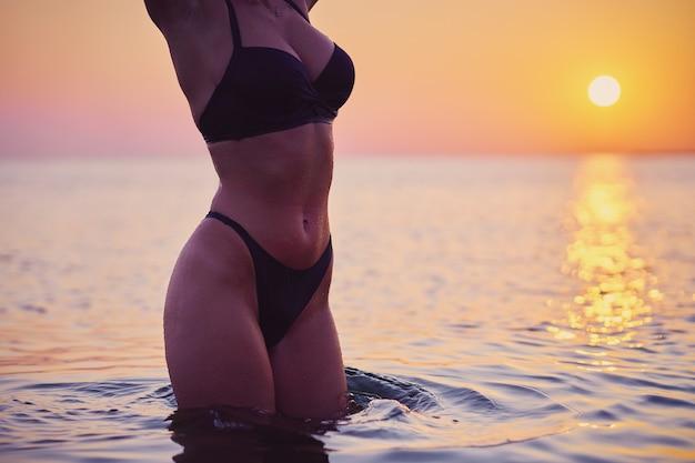 Силуэт сексуальная женщина позирует на рассвете на пляже
