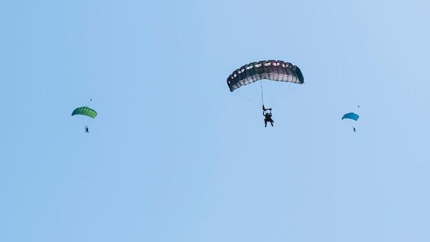青い澄んだ空を飛んでいるスカイダイバーのシルエット。