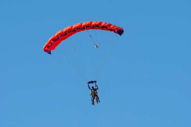 青い澄んだ空を飛んでいるスカイダイバーのシルエット