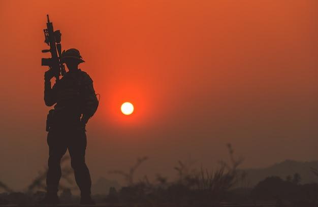 夕焼け空の兵士のシルエット。機関銃のパトロールを持つ兵士