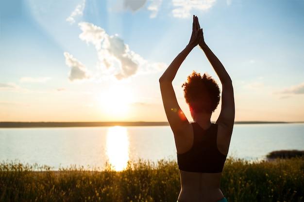 Силуэт йоги спортивной девушки практикующих в поле на рассвете.