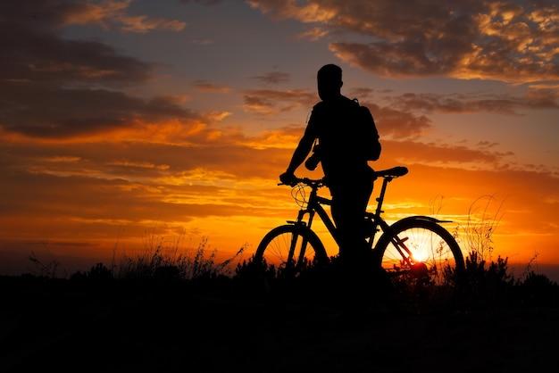 Силуэт человека спорта, езда на велосипеде на лугу на красивом закате.