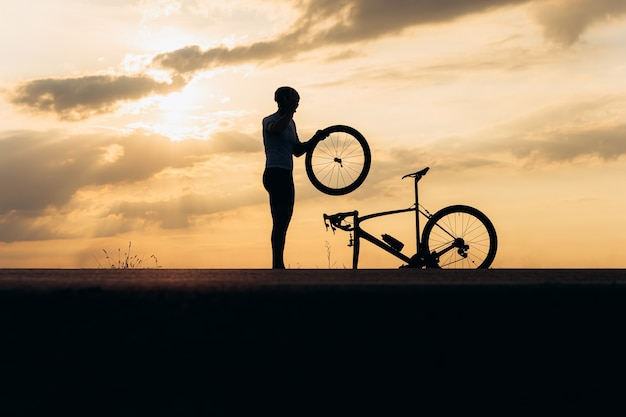 Силуэт сильного человека в шлеме и спортивной одежды, фиксирующий колесо на велосипеде на открытом воздухе