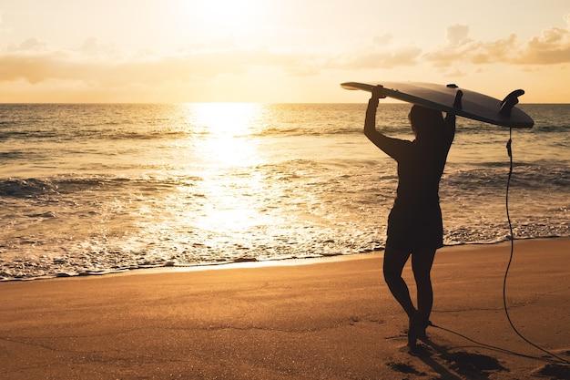 Силуэт женщины-серфера, несущей свои доски для серфинга на пляже заката с солнечным светом