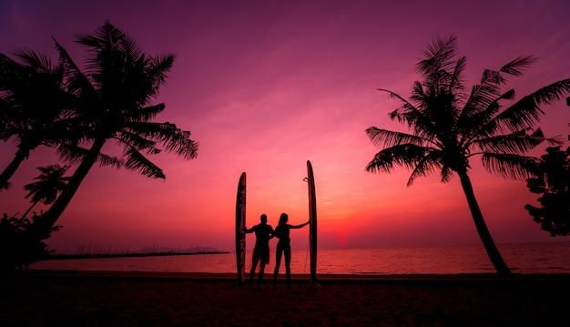 日没で長いサーフボードを保持しているサーファーカップルのシルエット