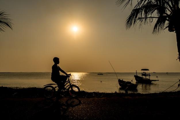 彼の休日休暇のリラックスできる時間のビーチの近くの夕日の下で自転車に乗る少年のシルエット