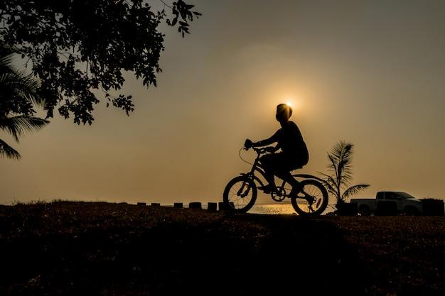 彼の休暇休暇のリラックスした時間にビーチの近くの夕日の下で自転車に乗る少年のシルエット