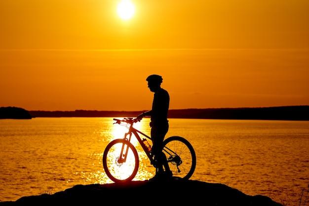 Силуэт велосипедиста, едущего на спортивном велосипеде на закате. концепция активного образа жизни.