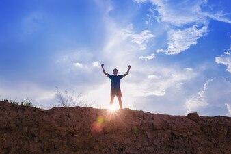 手に立っているランナーのシルエットは、レンズのフレアで崖の上に勝利を収める
