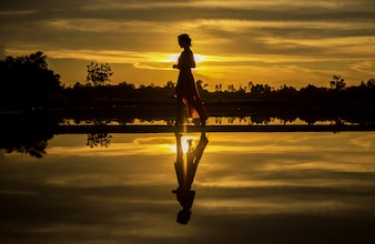 Silhouette of the woman walking at the beach during beautiful sunset
