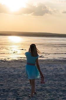 Силуэт женщины с длинными волосами, бегущими в море во время золотого заката. вариант фото.