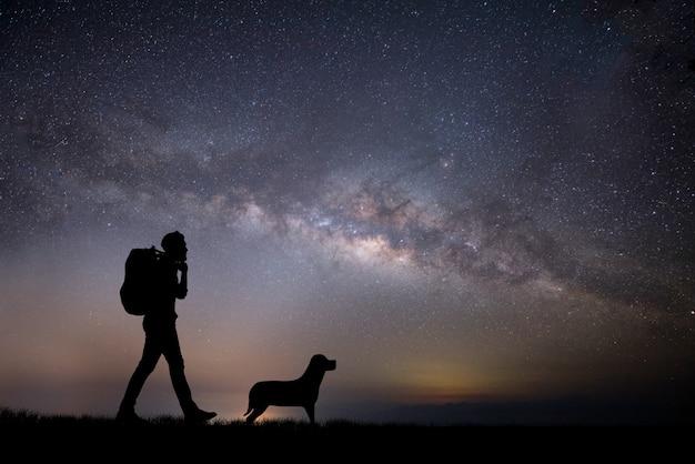 夕日を歩いている若いバックパッカーの男のシルエット。