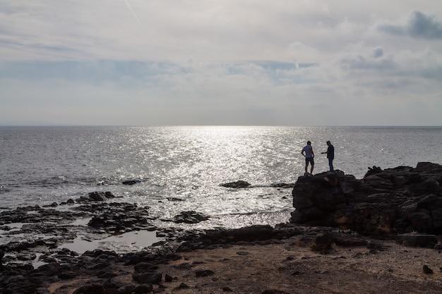 바다 옆 큰 바위에 서 있는 두 남자의 실루엣. 스페인 란사로테.