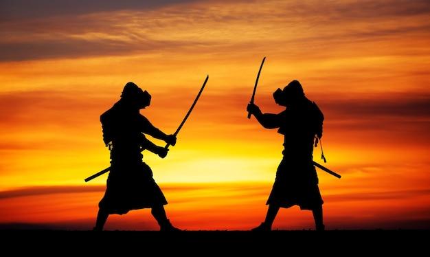 Силуэт двух самураев на дуэли. картина с двумя самураями и закатным небом