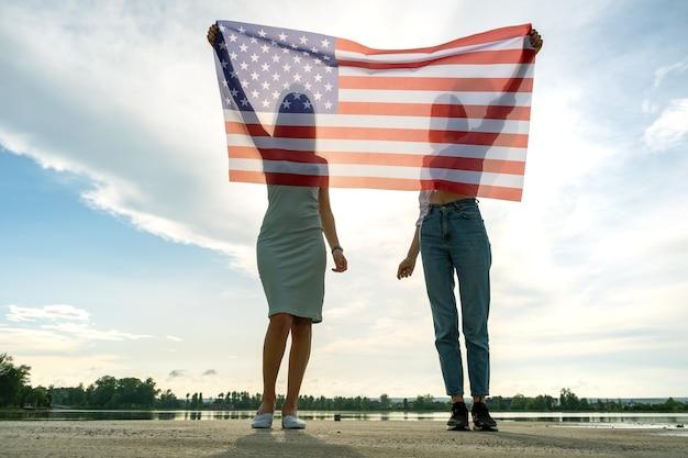 Силуэт двух молодых друзей женщин, держащих национальный флаг сша