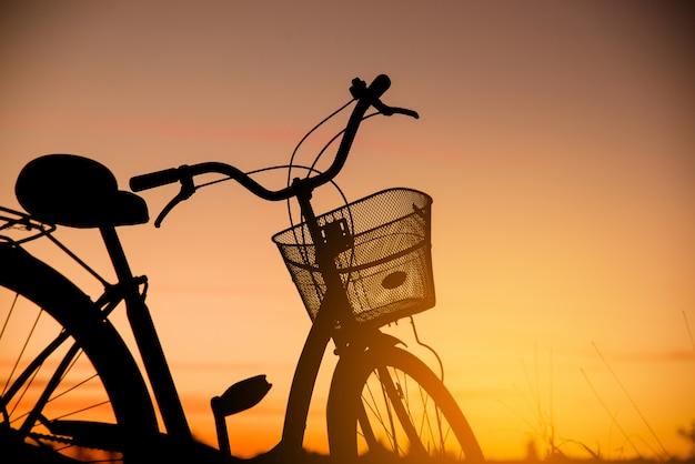 석양에 빈티지 자전거의 실루엣 무료 사진